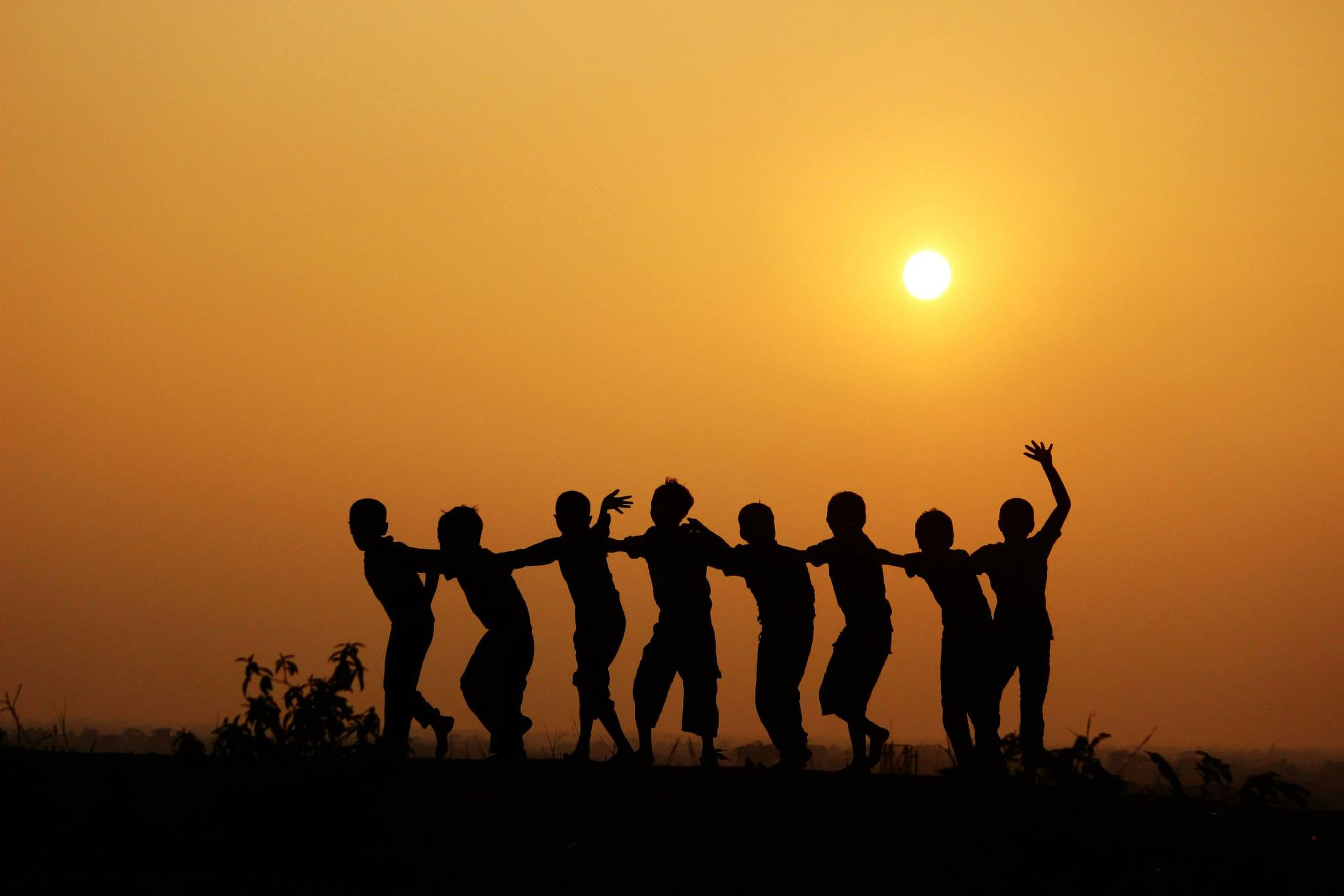 sunset, silhouette, orange color, copy space, sun, clear sky, men, leisure activity, togetherness, lifestyles, sky, beauty in nature, landscape, scenics, nature, tranquil scene, standing, large group of people, field
