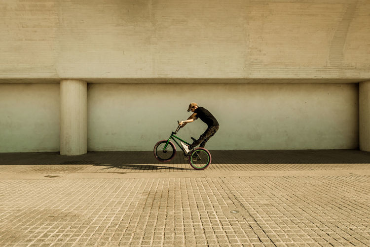 Man riding bicycle on footpath against wall