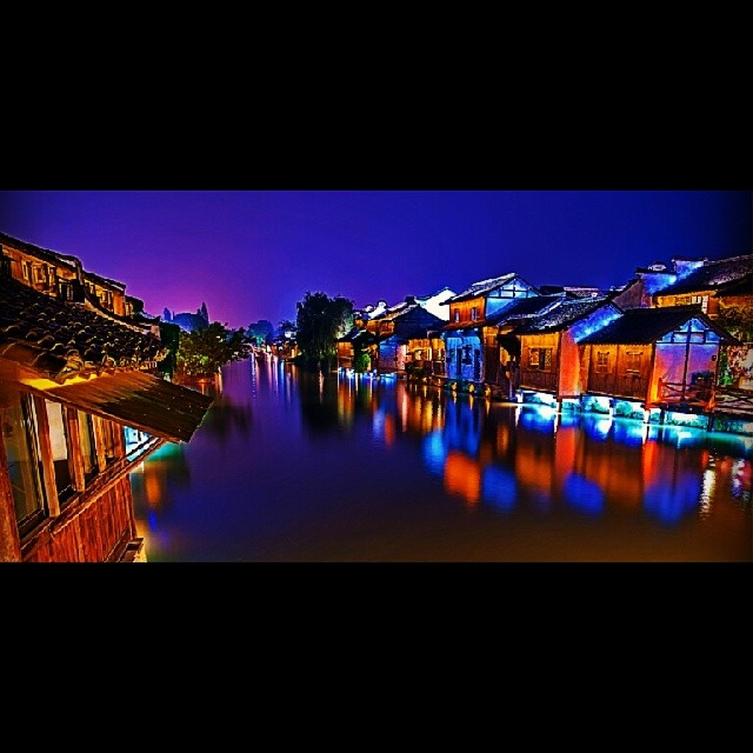 architecture, built structure, building exterior, reflection, water, illuminated, blue, clear sky, waterfront, residential structure, river, sky, house, city, night, residential building, canal, copy space, standing water, outdoors