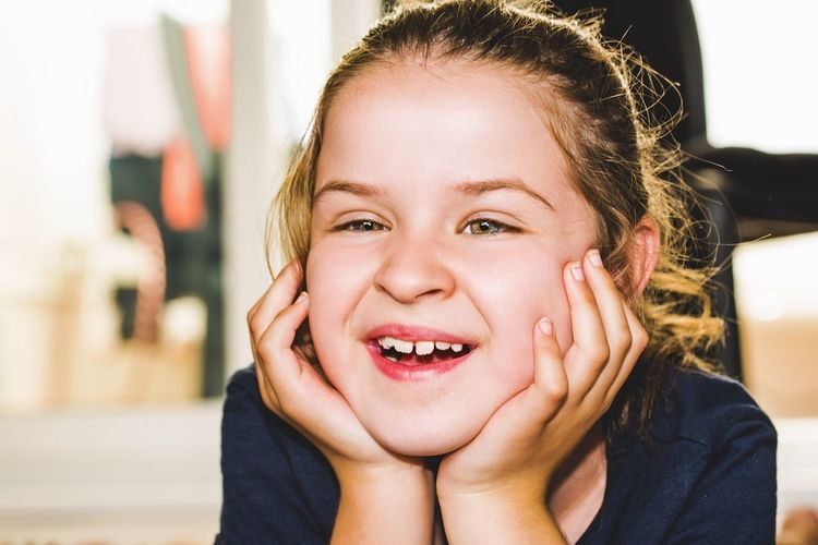 Smiling Girl With Hands On Chin Looking Away While Sitting At Home