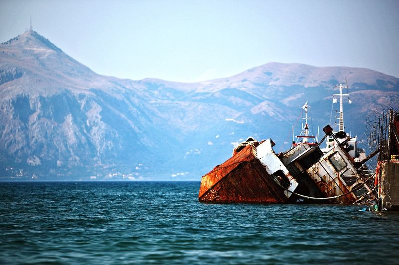 Rusty ship in sea by mountains
