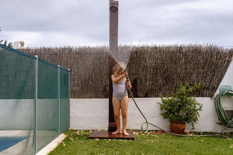 Woman standing in yard against sky