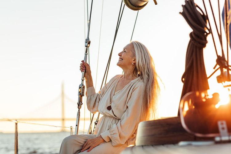 Beautiful senior woman in boat sailing on sea against sky