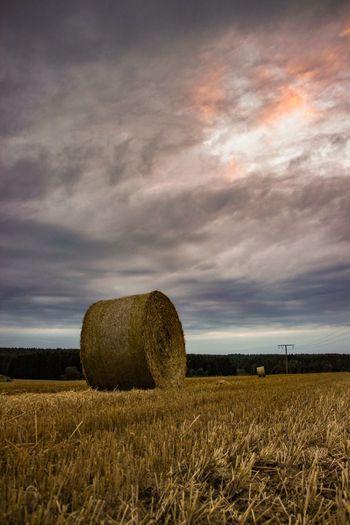 Hay bales in field against cloudy sky