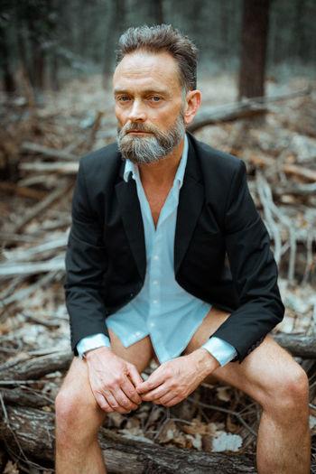Portrait of man sitting on sidewalk