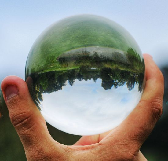 Close-up of human hand holding crystal ball against trees