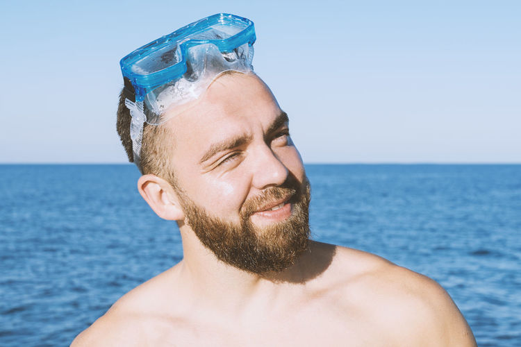 Close-up of shirtless man at sea