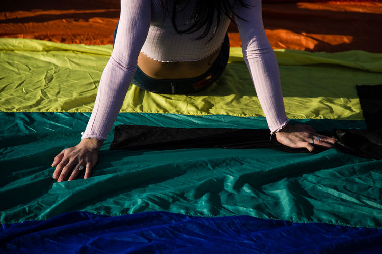Midsection of woman sitting on rainbow flag