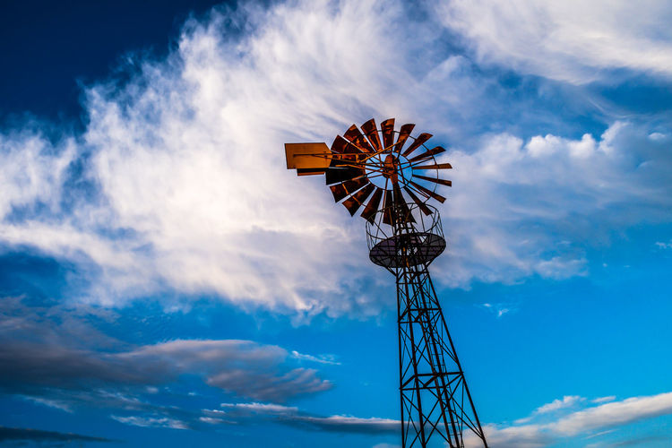 Low angle view of water pump windmill against clouds and sky