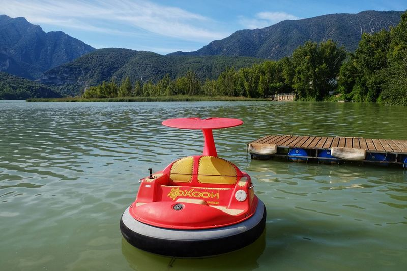 Red boat floating on lake against mountains