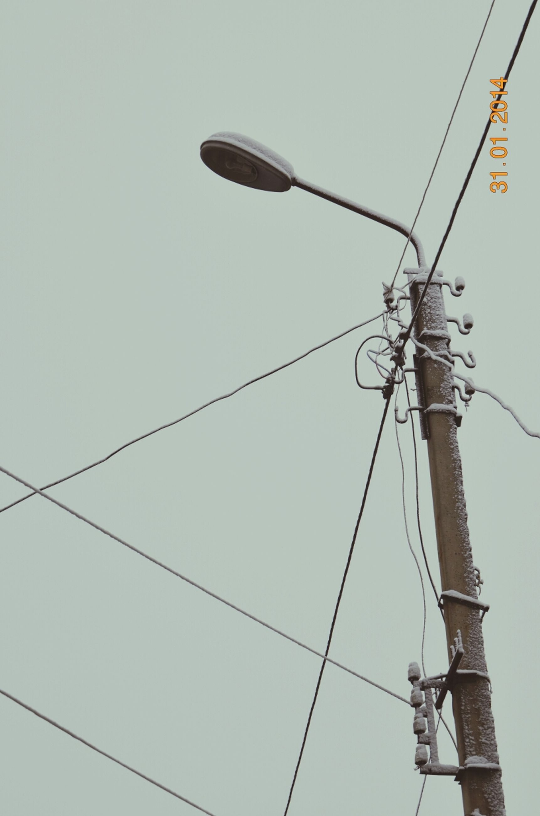 low angle view, power line, cable, electricity, clear sky, power supply, connection, electricity pylon, technology, fuel and power generation, pole, complexity, hanging, copy space, sky, power cable, lighting equipment, day, outdoors, no people