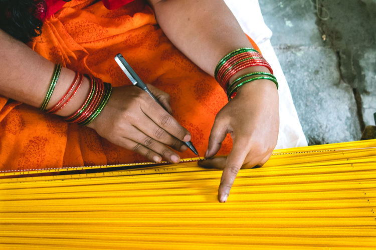 Midsection of woman marking yellow wood with marker at workshop