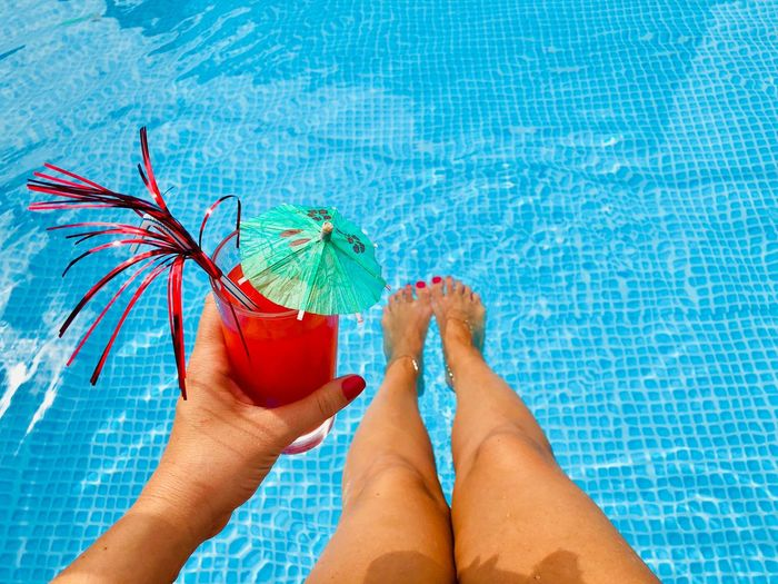 Woman's hand with red nails holding a glass of red orange juice with a small umbrella and a funny straw over the turquoise water of the pool Vacation Holiday Refreshment Beverage Sexy Tanned Legs Feet Cocktail Straw Umbrella Blood Orange Orange Fresh Smoothie Juice Cold Drink Drink Glass Red Nails Hands Hold Alone Woman Swimming Pool Pooledge Poolside Summer