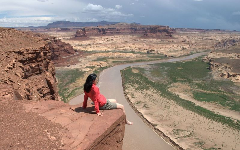 High angle view of woman sitting on cliff at desert