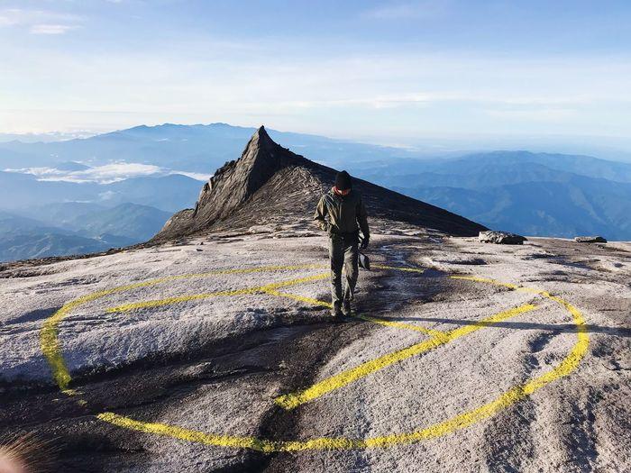 Man Standing On Helipad On Mountain Against Sky