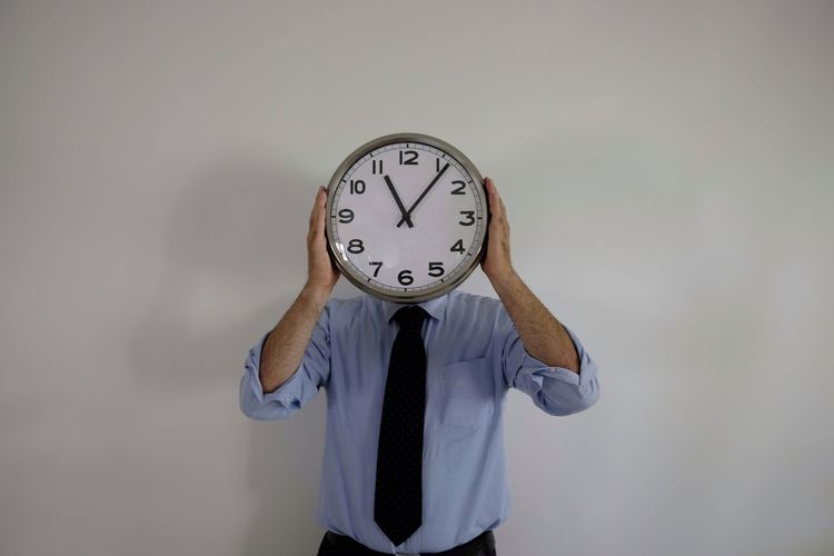 Businessman Covering Face With Clock While Standing Against Wall