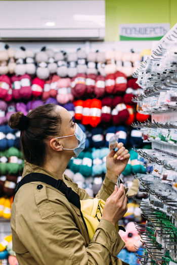 Woman in face mask selects beads products in handicraft store. shopping concept