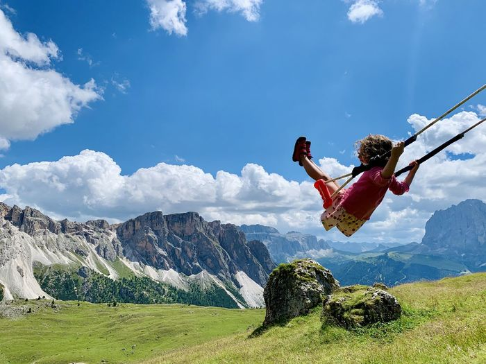 Woman jumping on mountain against sky