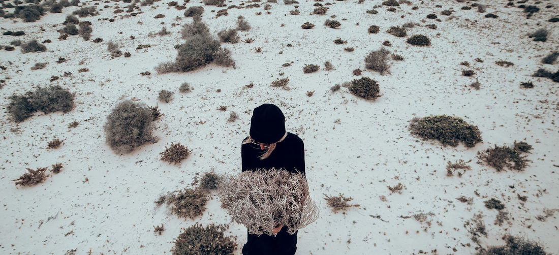 Fashion photo. girl in black clothes in the desert with a bouquet dead branches