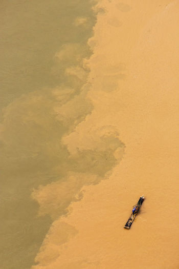 Aerial view of cormorant fisherman paddling on his bamboo raft at the li river, china