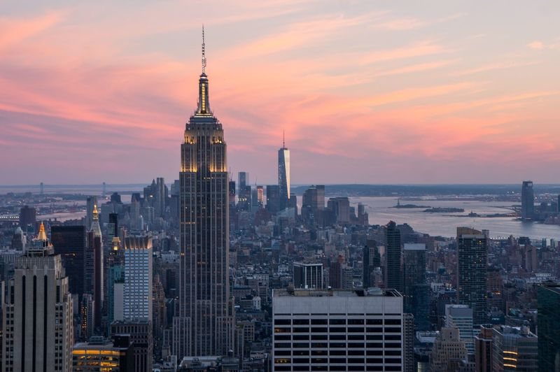 Empire state building in cityscape against sunset sky