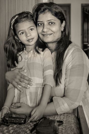 Portrait of mother and daughter sitting at home