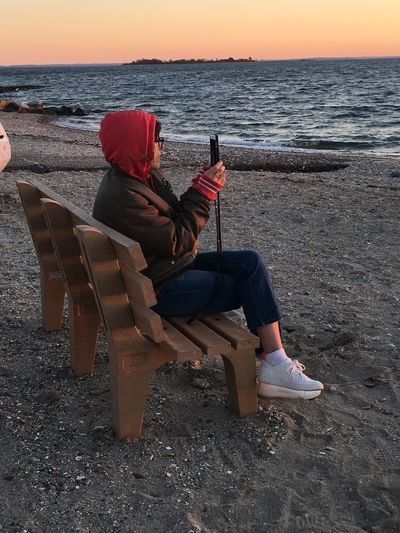 Sunset at the beach Sitting Sea Full Length One Person Real People Horizon Over Water Wireless Technology Lifestyles Leisure Activity Water Beach Nature Scenics Sunset Beauty In Nature Portable Information Device Technology Communication Relaxation Tranquility