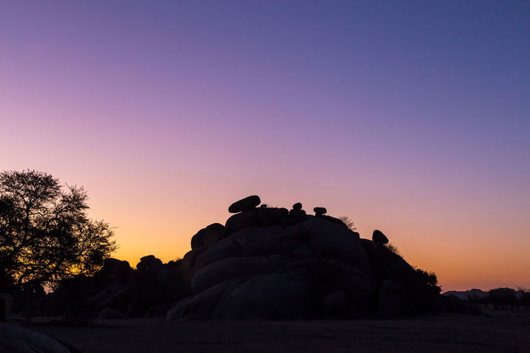 Silhouette rocks against clear sky during sunset