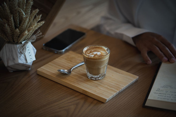 Coffee on Wooden Table with Book in Cafe Ijas Muhammed Photography Table Wood - Material Drink Food And Drink Coffee Indoors  Coffee - Drink Book Publication Refreshment One Person Coffee Cup Communication Mug High Angle View Cup Technology Pen Wireless Technology Sitting Glass Crockery