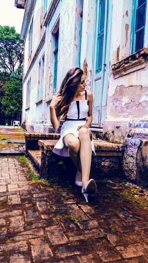 Beautiful woman sitting on retaining wall against abandoned building