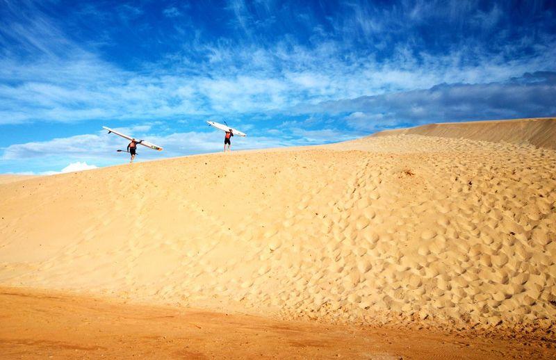 Men holding surf ski walking on shore at beach against sky