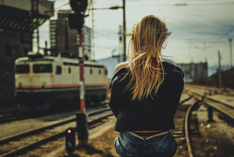 Rear View Of Woman With Blond Hair Against Railroad Track