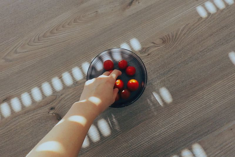 Cropped image of hand picking cherry tomatoes from bowl on wooden table