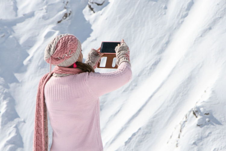 Midsection of woman photographing in snow