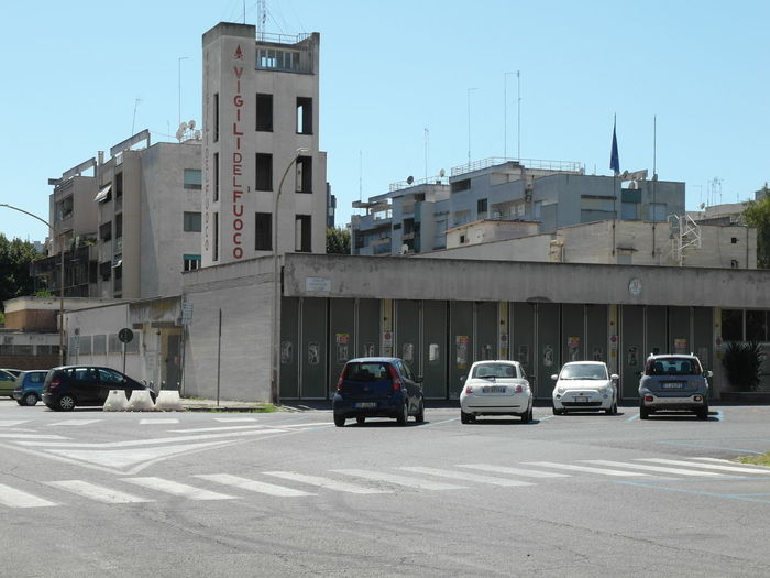 Cars on street by buildings in city against clear sky