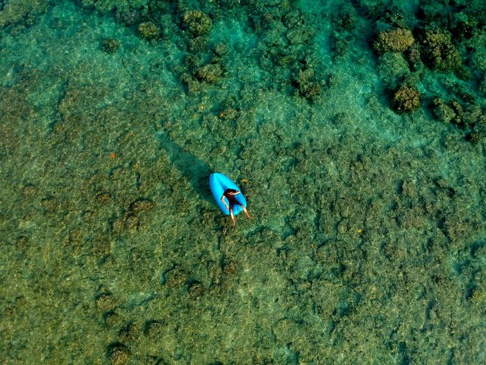 Aerial view of man over inflatable raft in sea