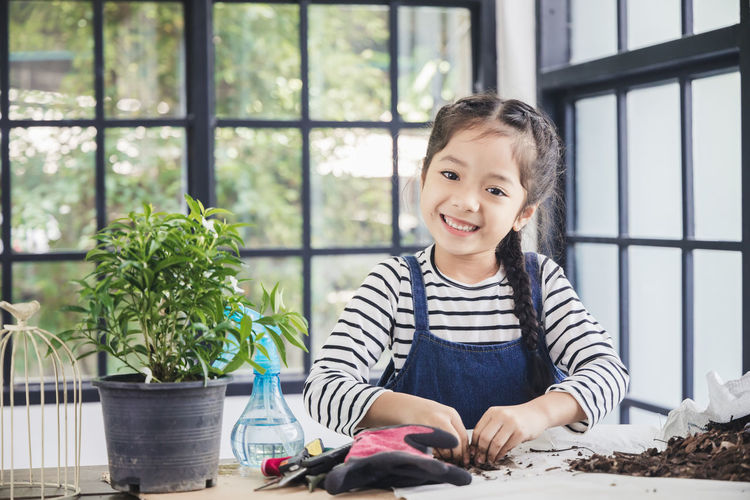 Portrait of smiling girl sitting on window
