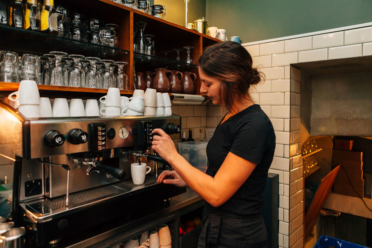 Side View Of Barista Making Coffee In Cafe