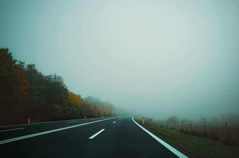Empty Road By Trees During Cloudy Sky