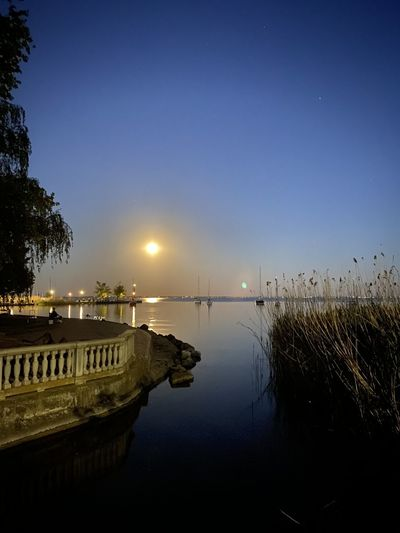 Scenic view of lake against clear blue sky at night