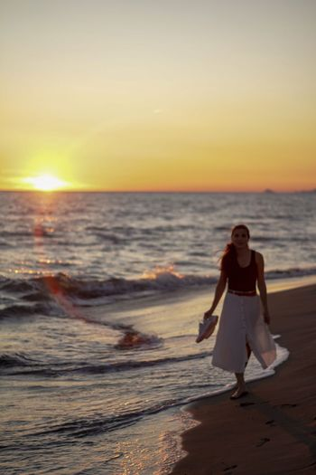 Full length of woman on beach during sunset