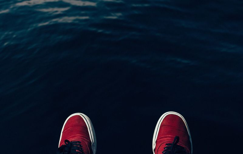 Close-up of cropped shoes against calm water