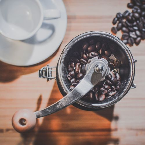 Directly above shot of coffee beans in grinder on table