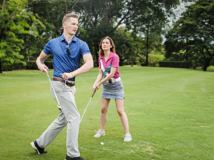 Full length of couple playing golf