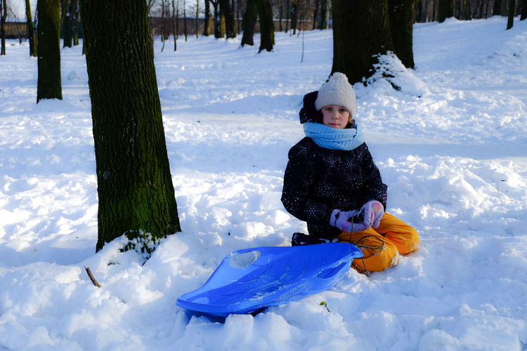Portrait Of Boy With Sled Kneeling On Snow Covered Field