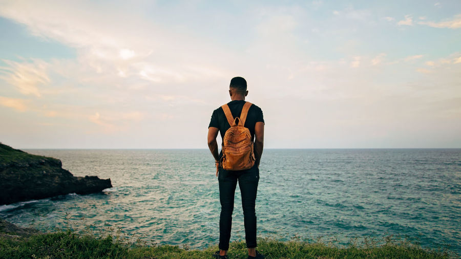Fashion Grass Bag Beauty In Nature Casual Clothing Cloud - Sky Horizon Horizon Over Water Looking At View Nature Non-urban Scene One Person Outdoors Real People Rock Scenics - Nature Sea Sky Standing Water The Modern Professional It's About The Journey