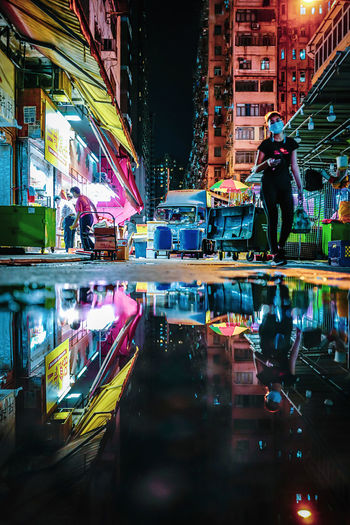 People walking on illuminated street by buildings at night