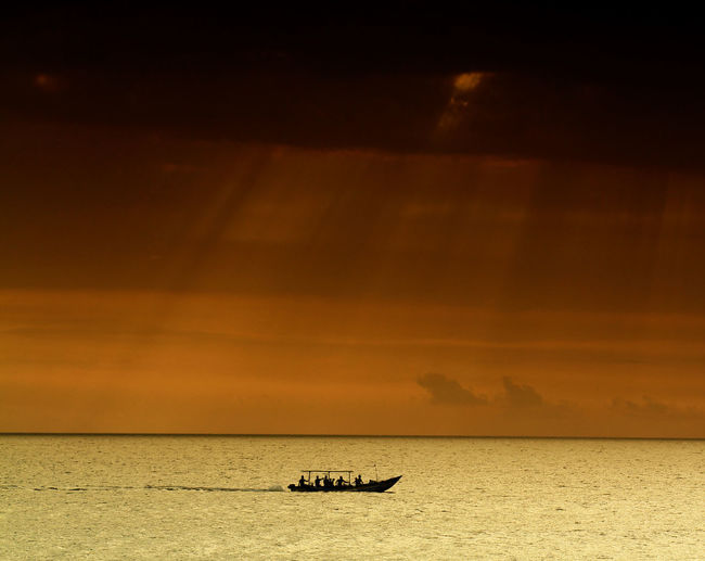 Silhouette of boat sailing in sea at sunset