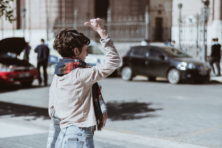 Side view of woman hitchhiking on street