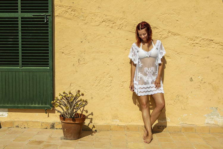 Young woman standing at a yellow wall Mallorca Mediterranean  One Person Front View Young Adult Women Young Women Real People Leisure Activity Hairstyle Lifestyles Beautiful Woman Bikini Beach Dress Wall - Building Feature Full Length Standing Outdoors Potted Plant Building Exterior Portrait